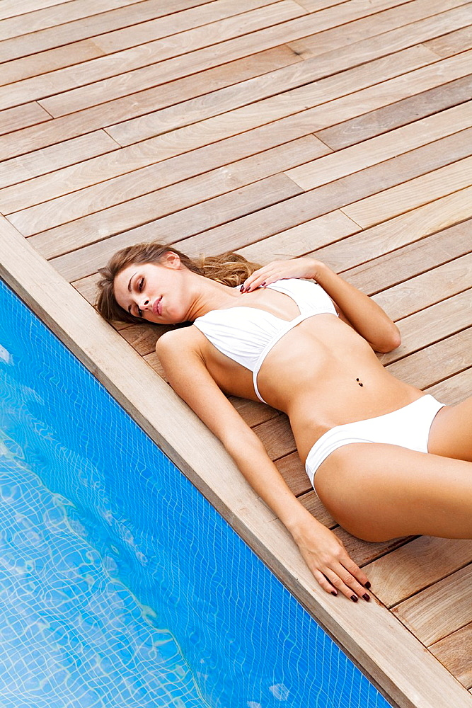 Blonde beautiful woman resting and lying down by the pool - 817-254936