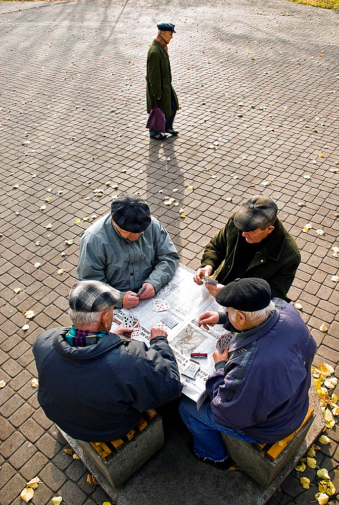Group of old men playing cards in Wohrmanns Garden and man walking nearby, Riga, Latvia, Europe