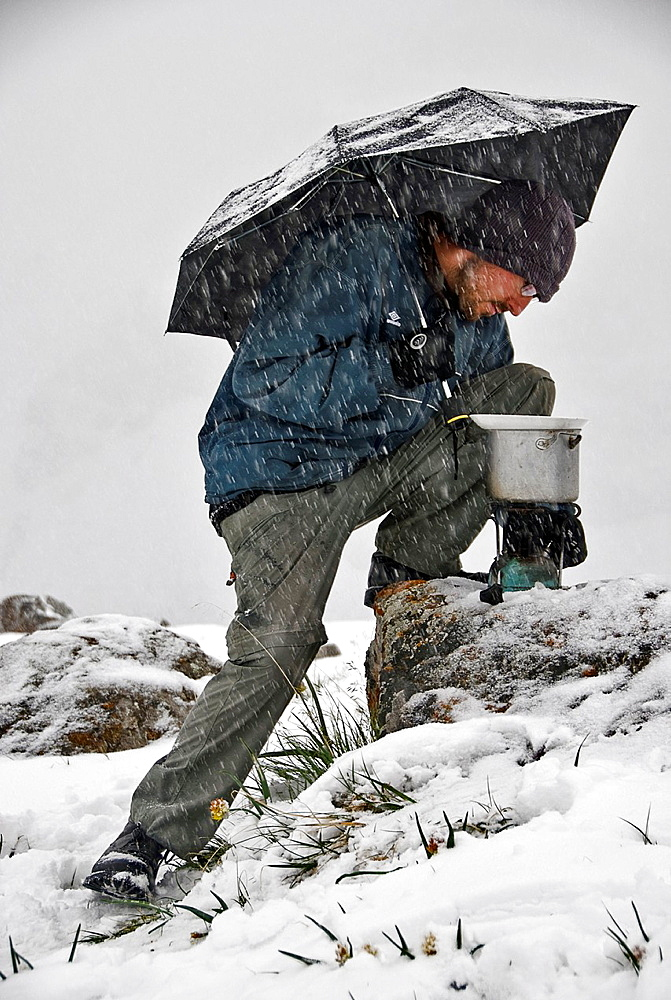 Man with umbrella trying to cook under a heavy snow fall Ala Kol lake, Kyrgyzstan