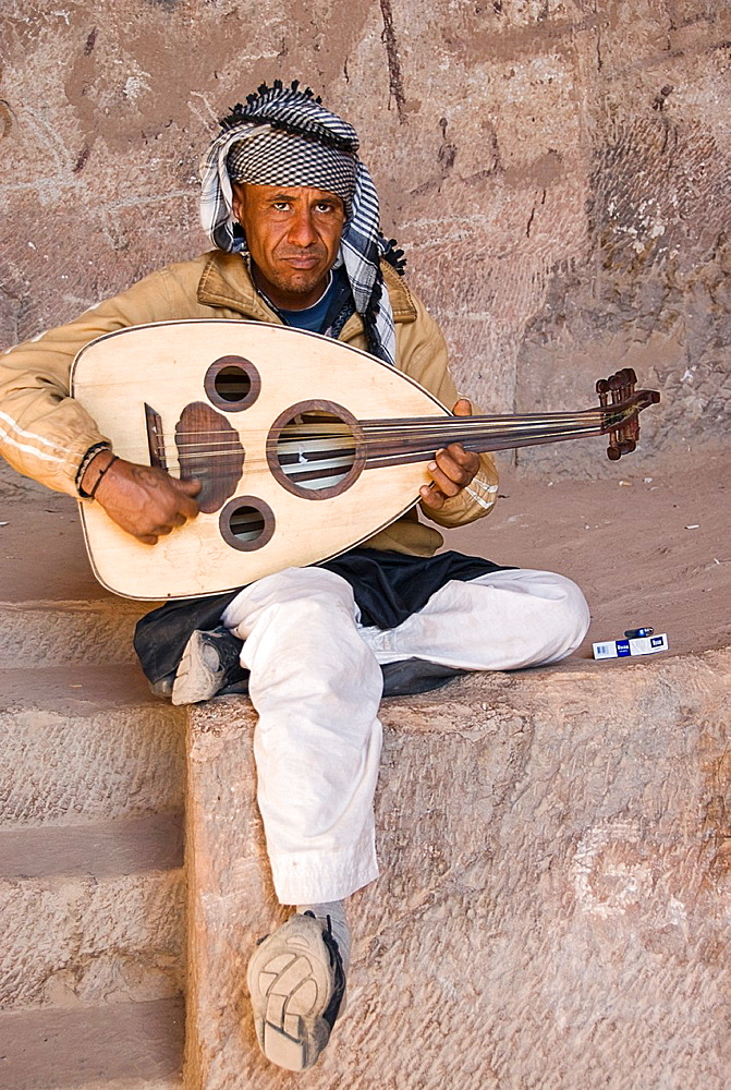 Beduin playing a sort of lute inside the monastery of Petra, Jordan, Asia