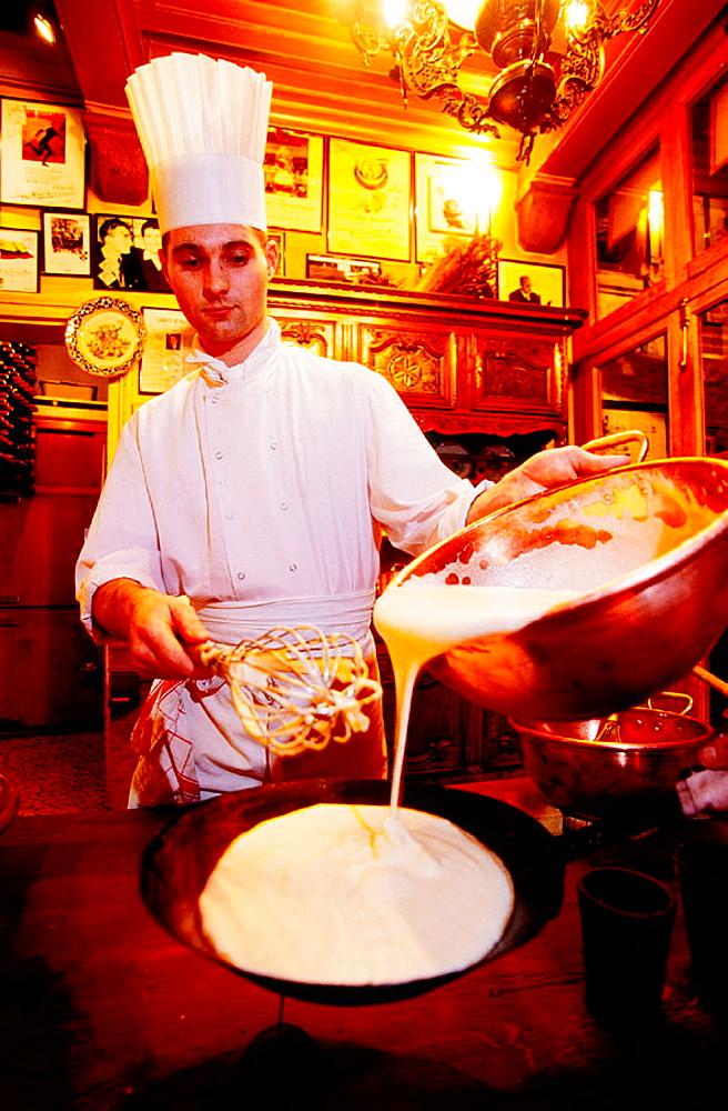 Restaurant 'La Mere Poulard': waiter preparing an omelette in front of customers, Mont St, Michel, Normandy, France