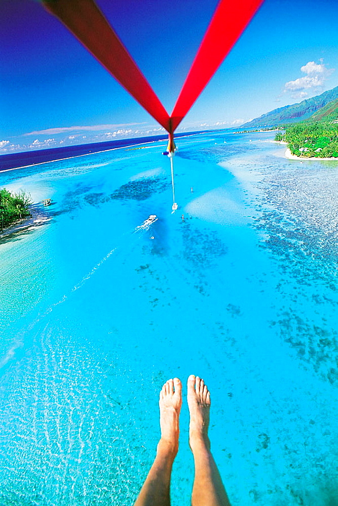 Parasailing over the Moorea lagoon, photographers feet at fore, French Polynesia
