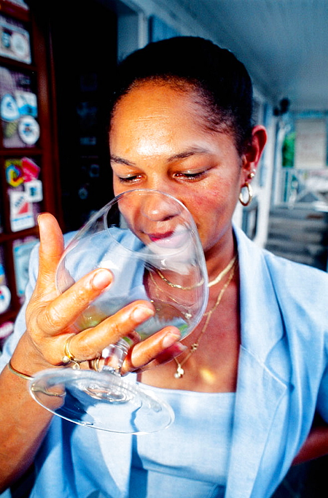 Woman tasting rum, Hell-Bourg, Salazie cirque, Reunion Island (France)