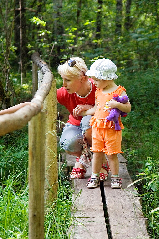 Mother with Kid Girl Standing on Wooden Boardwalk with Fence in Forest - 817-266571