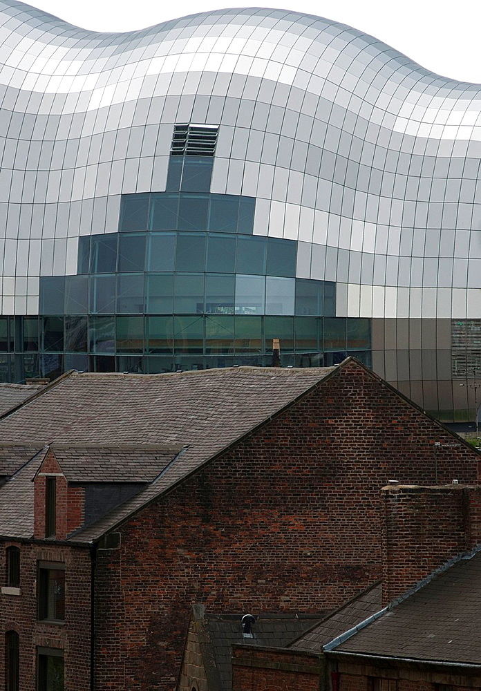 The ultra modern Sage contrasts with old brick buildings in the foreground Newcastle upon Tyne, UK