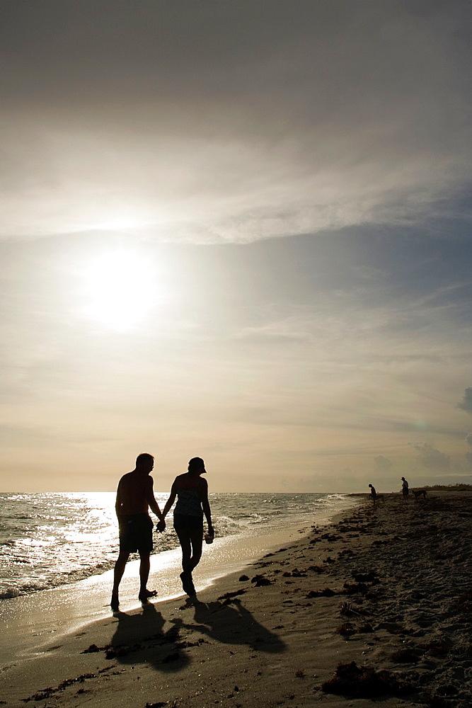Couple walking hand-in-hand down Bowmans Beach, Sanibel Island, Florida - 817-280698