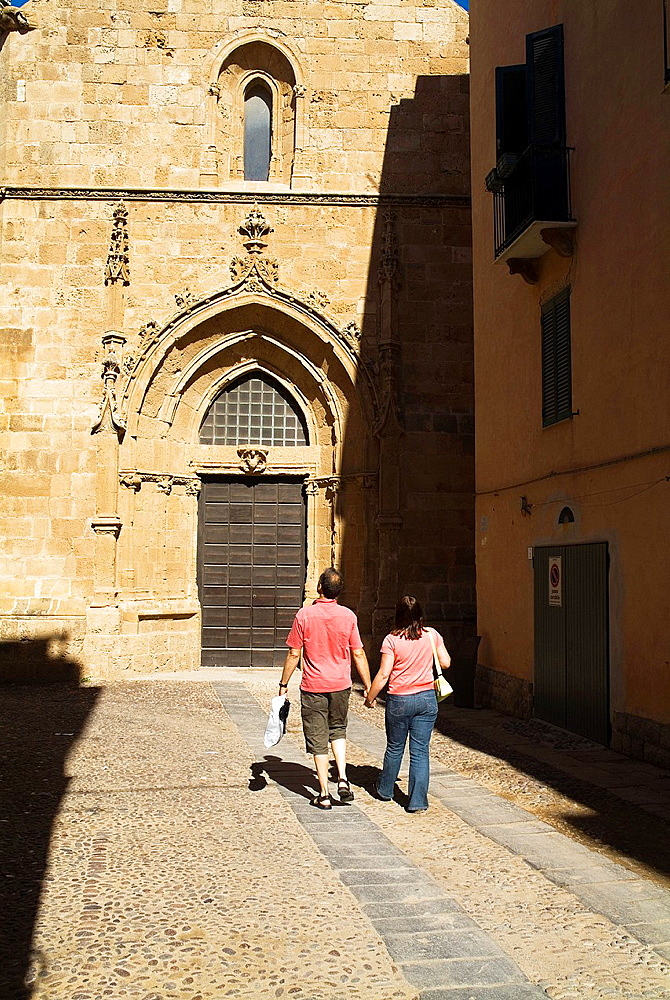 St Mary bell tower ALGHERO SARDINIA Tourist couple at old door Cathedral Santa Maria campanile