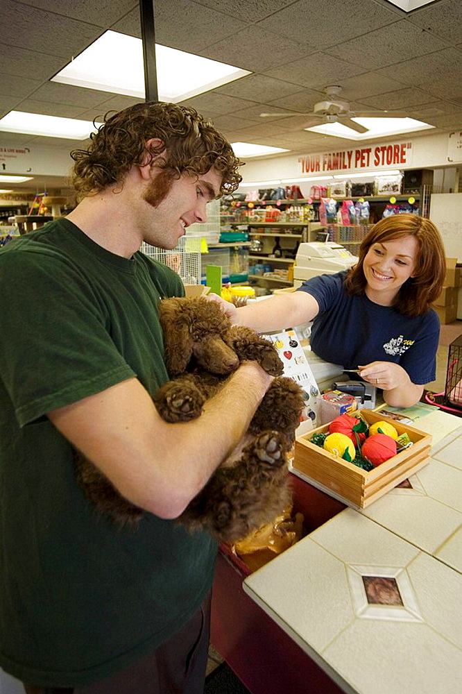 A customer purchases a dog at a pet shop in Laguna Niguel, CA, USA