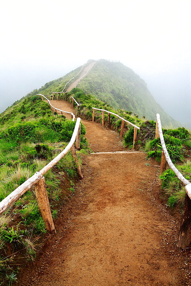 Empty walking trail in foggy weather disappearing into the low clouds, nearby Sete Cidades crater Sao Miguel island, Azores, Portugal