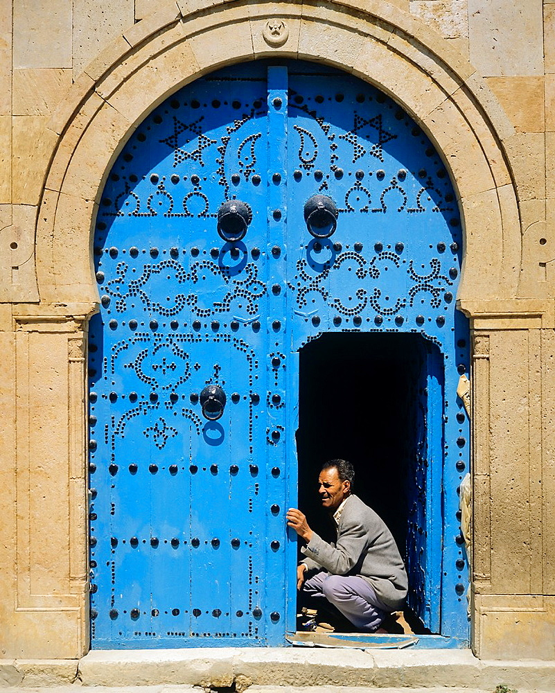 Man repairing a traditional blue studded door, Sidi Bou Said village, Tunisia