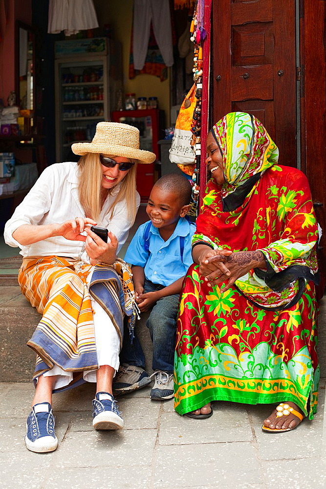 Tourist showing photos on her smart phone to local woman & child in East African market.