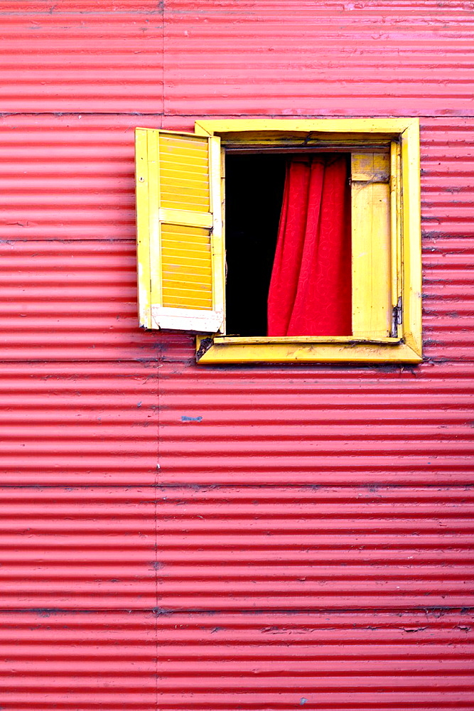 Red house with one open, yellow window, in El Caminito, La Boca, Buenos Aires, Argentina, South America