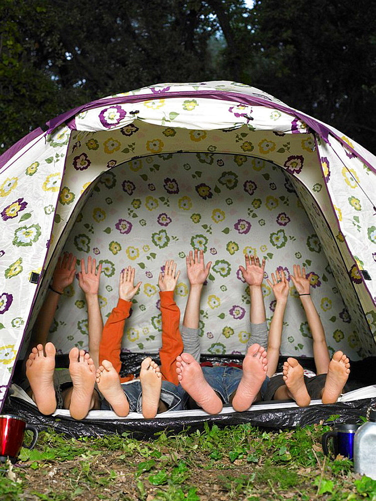 Four friends stretching in tent