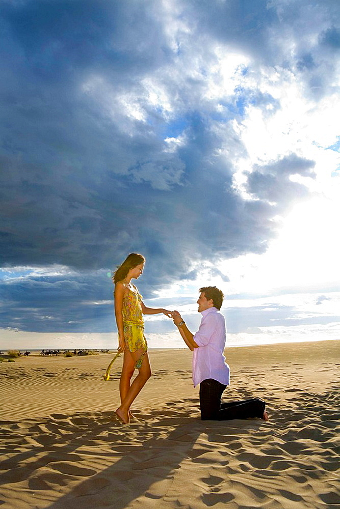 Man on knees proposes marriage in sand