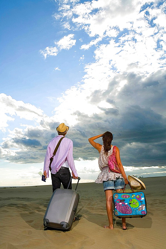 Traveling couple walk in sand