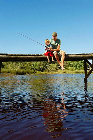 Father and son fishing from jetty, Man and young boy sitting on jetty fishing