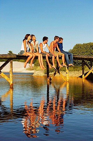 Group of young people sitting on jetty, Two teenage girls and three young men are relaxing in the sun on jetty, They are reflected in the water