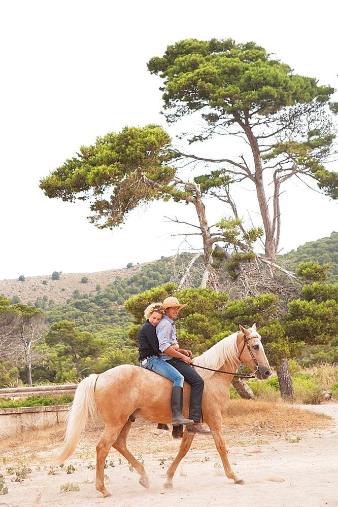 woman and man riding together on a horse