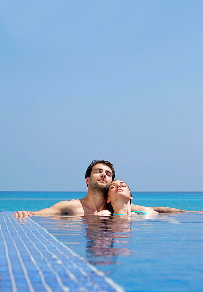 Couple relaxing in infinity pool, Couple relaxing in infinity pool