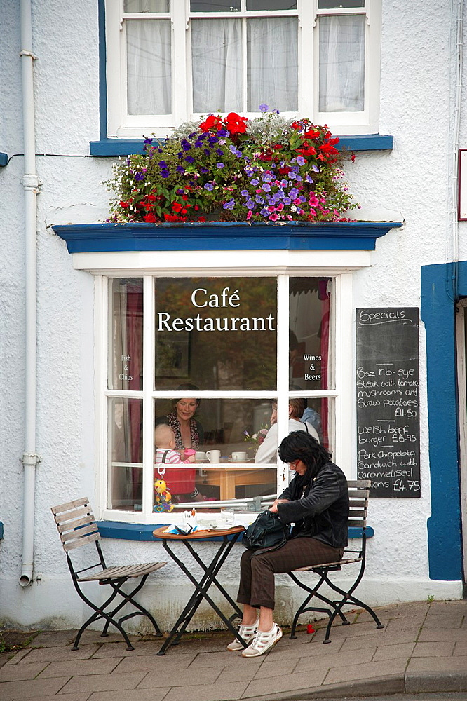 People eating breakfast at an outdoor cafe, Newport, Pembrokeshire Wales UK