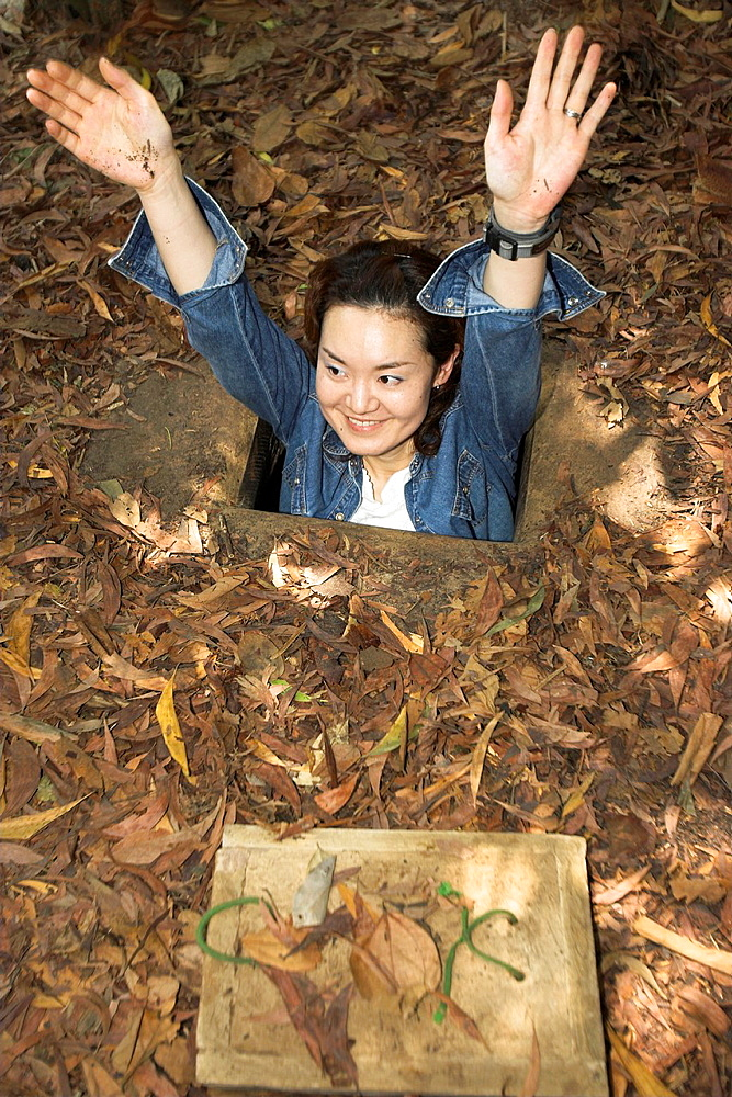 Woman tourist with arms above head demonstrates how to enter the Cu Chi Tunnels Vietnam