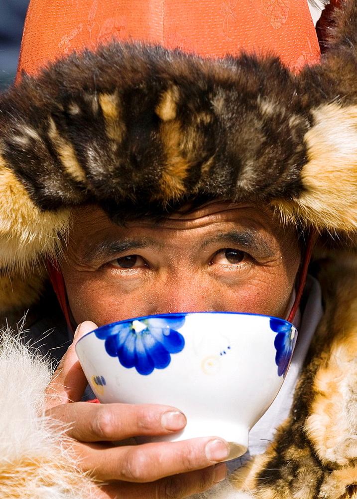 A Kazakh eagle hunter enjoys a hot cup of milk tea.