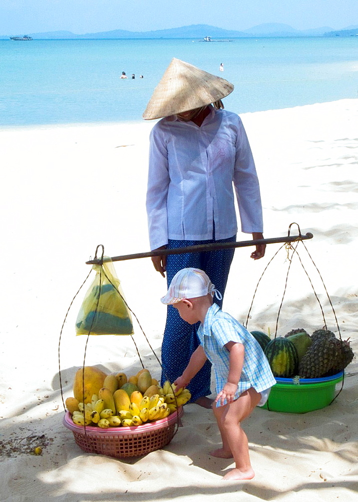 Small boy grabs banana bunch conical hat woman fruit vendor looks on Long Beach Phu Quoc Island Vietnam