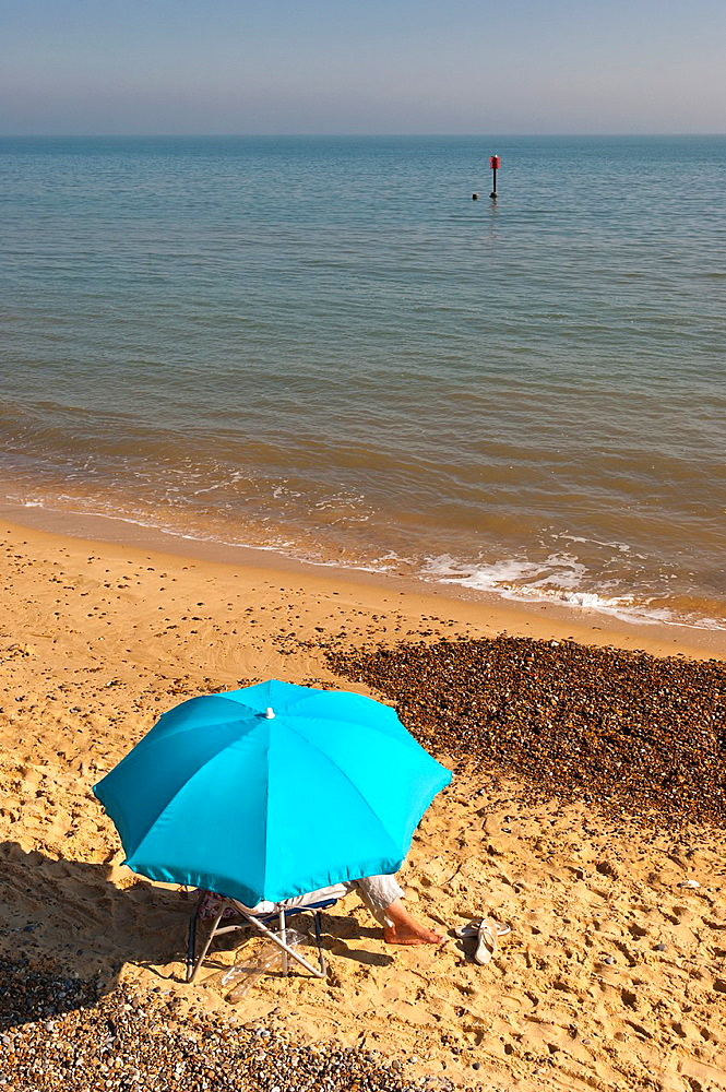 A person sitting under an umbrella on the beach in the summer in Southwold, Suffolk, England, Britain, Uk