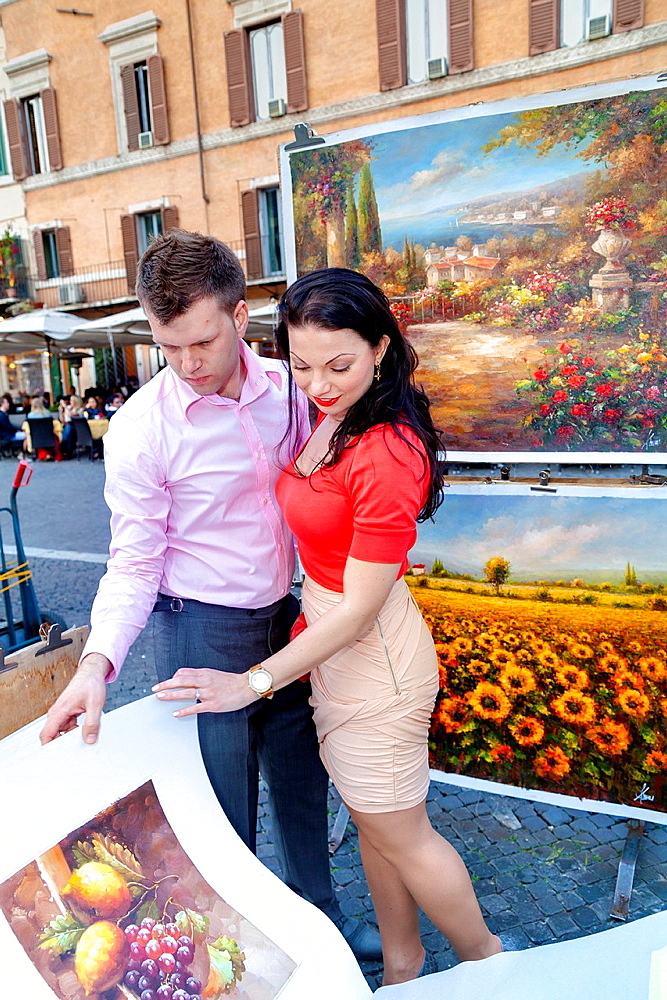 Couple flipping through art posters in Piazza Navona Rome Italy