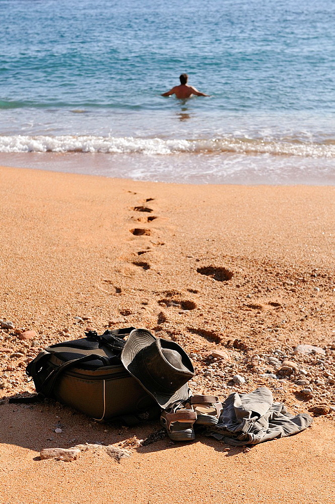 Hat and clothes abandoned at seashore and man bathing in the sea, Costa Brava, Catalonia, Spain, Europe