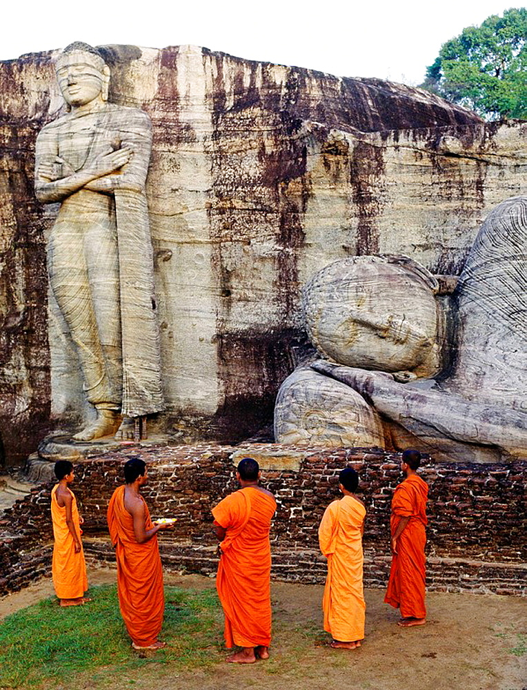 Praying at sunrise, Giant Buddha, Kalu Gal Vihara, Polonnaruwa, Sri Lanka medieval capital (established as the first city of the land in the 11th century), Sri Lanka