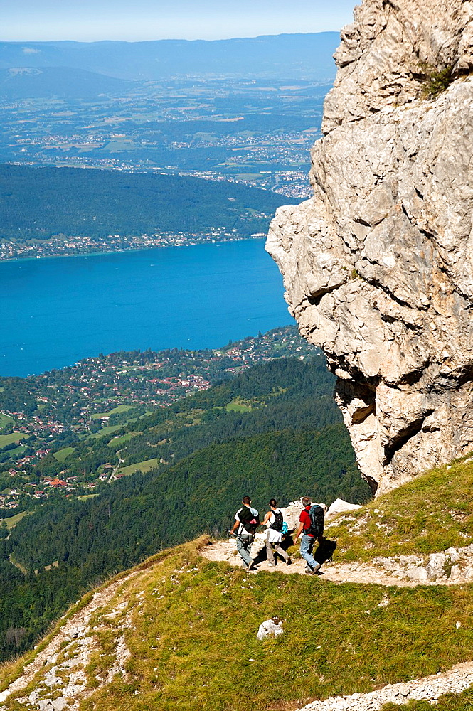 Hikers ascending on a narrow trail to the Tournette refuge in the Bornes Mountains Massif des Bornes above the Lake of Annecy Lac d´Annecy, Annecy, Haute-Savoie, France