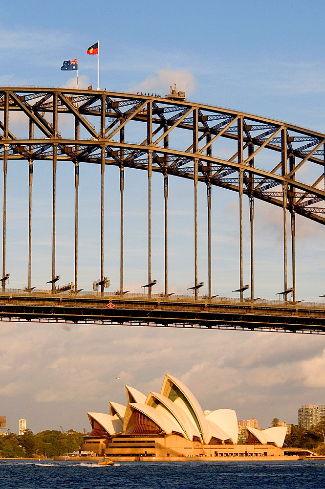 Sydney Harbour Bridge and Opera House, with Australian and Aboriginal flags flying from the top of the span