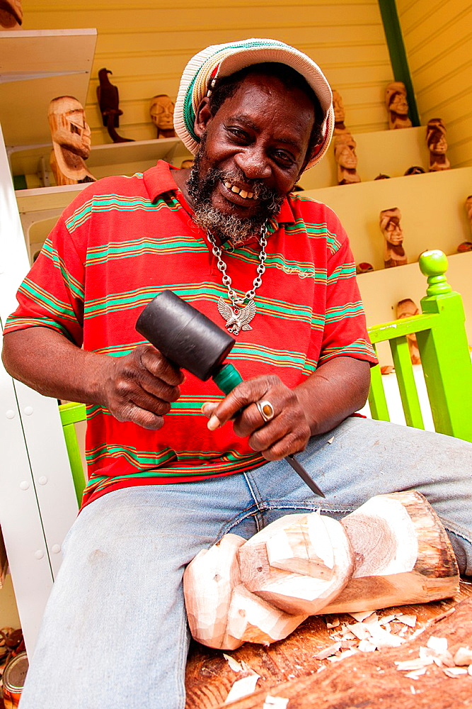 A wood carver works at the Straw Market in Nassau , Bahamas