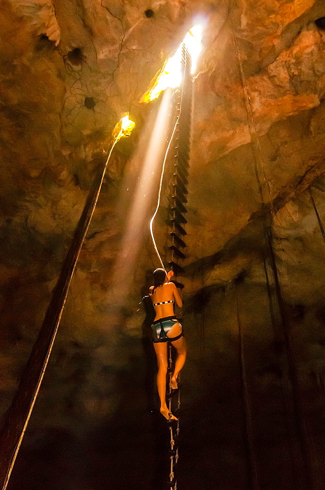 People rappelling into a cenote, a large limestone sinkhole which is part of the world´s longest underwater river, Riviera Maya, Mexico