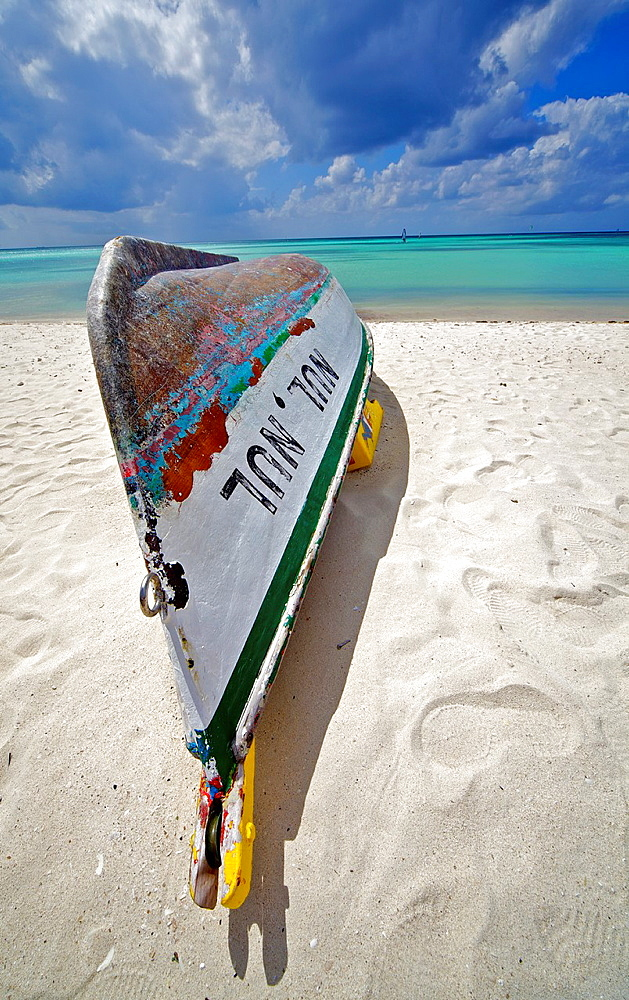 Shipwreck of a Wooden Boat on the Coastline of the Turquoise Water of the Carabbean Sea with Storm Clods on the Horizon