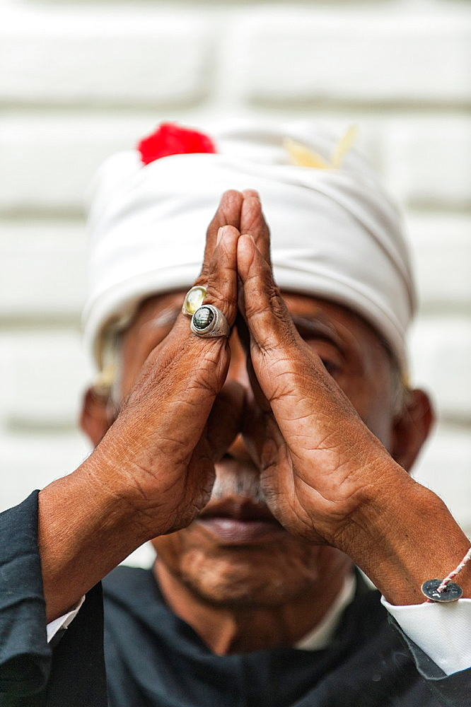 An elderly man meditates in front of a white wall