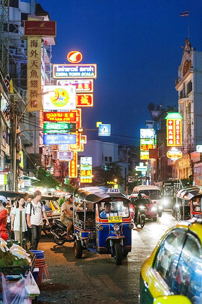 A Tuk Tuk driving through the streets of Bangkok at night