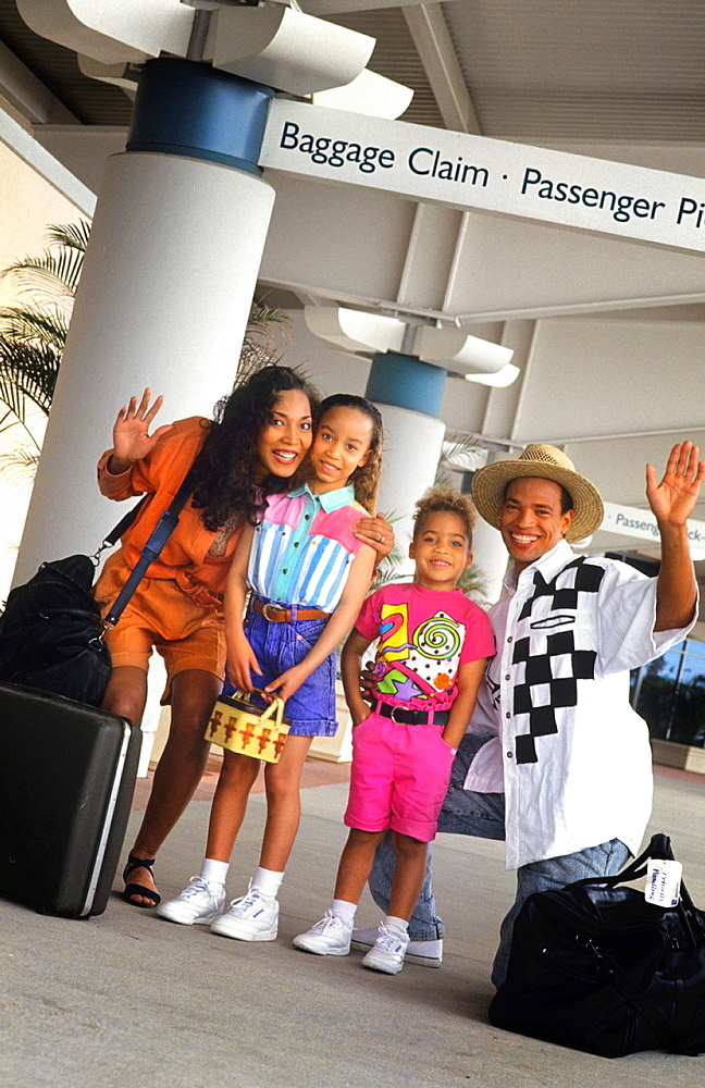 Black african american family at airport on holiday getting ready to travel together and have fun waving