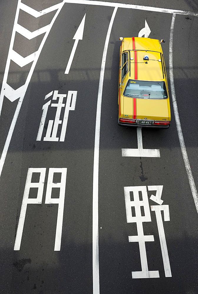 Aerial view of yellow Tokyo Taxi on a road in Tokyo Japan