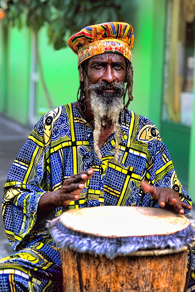 Colorful Rasta Jamaican Reggae performer on drum in costume at Harbour in St John Antigua - 817-417423
