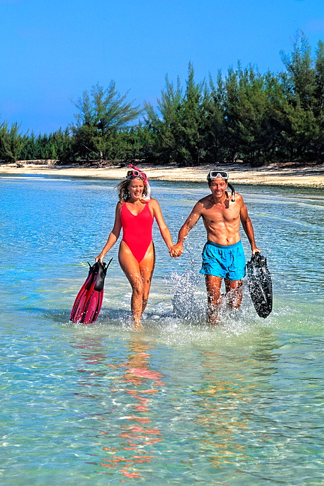 Couple 30s having fun at beach on vacation in Caribbean Mexico running in blue water with dive gear