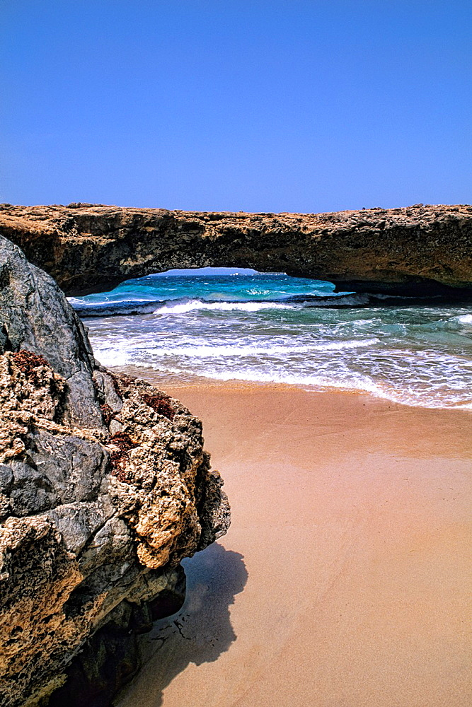 Beach and Rocks of the famous Natural Bridge colorful vacation in Aruba