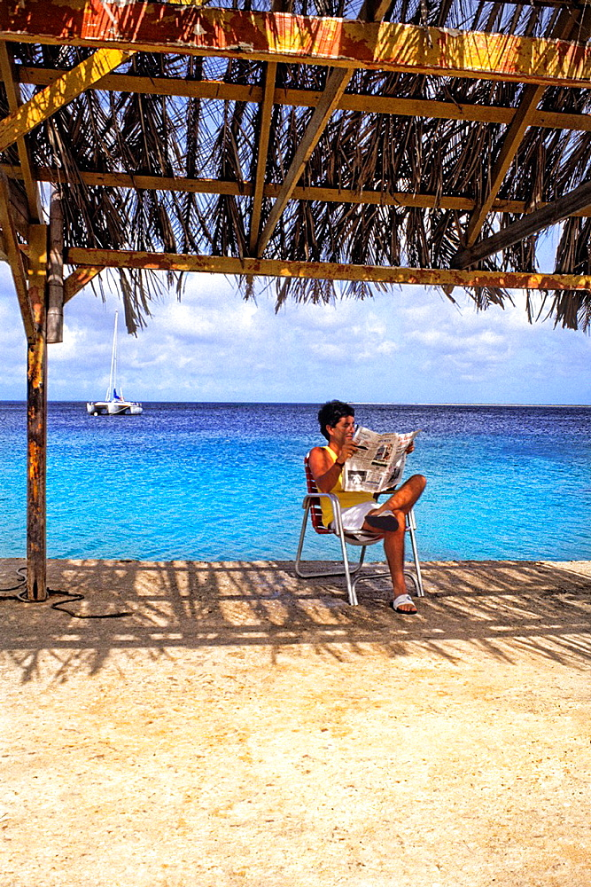 Man relaxing reading the newspaper by ocean in Bonaire on holiday vacation