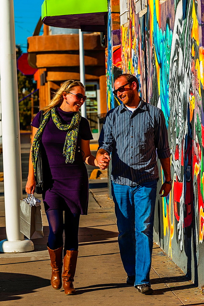Couple walking along Central Avenue historic Route 66 in Nob Hill, a mural of comic book super heroes in background, Albuquerque, New Mexico USA