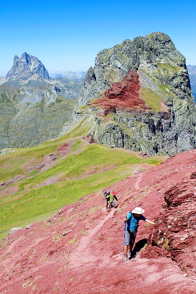 Hikers walking to summit of Anayet, an old volcano in Tena valley, and view of Midi d¥Ossau Peak France  Formigal  Sallent de Gallego  Pyrenees  Huesca province  Aragon  Spain