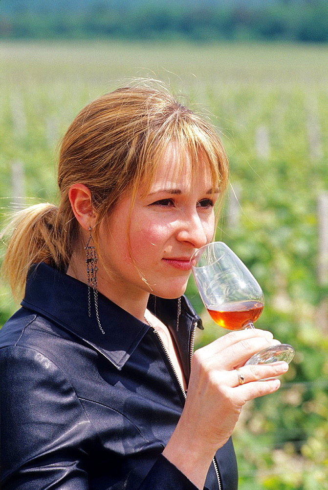 Young woman tasting a french wine Rose des Riceys in the vineyards, Aube department, Champagne-Ardenne region, France, Europe
