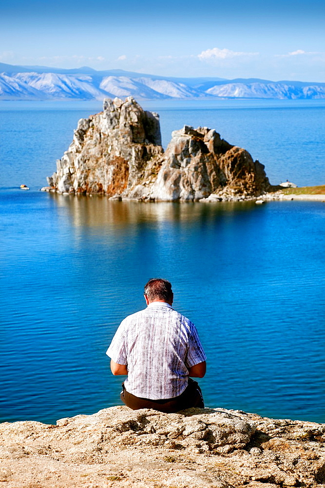 Olkhon, Russia-July 27, 2010  A man sitting on a cliff reading a book in front ok Cape Burkhan