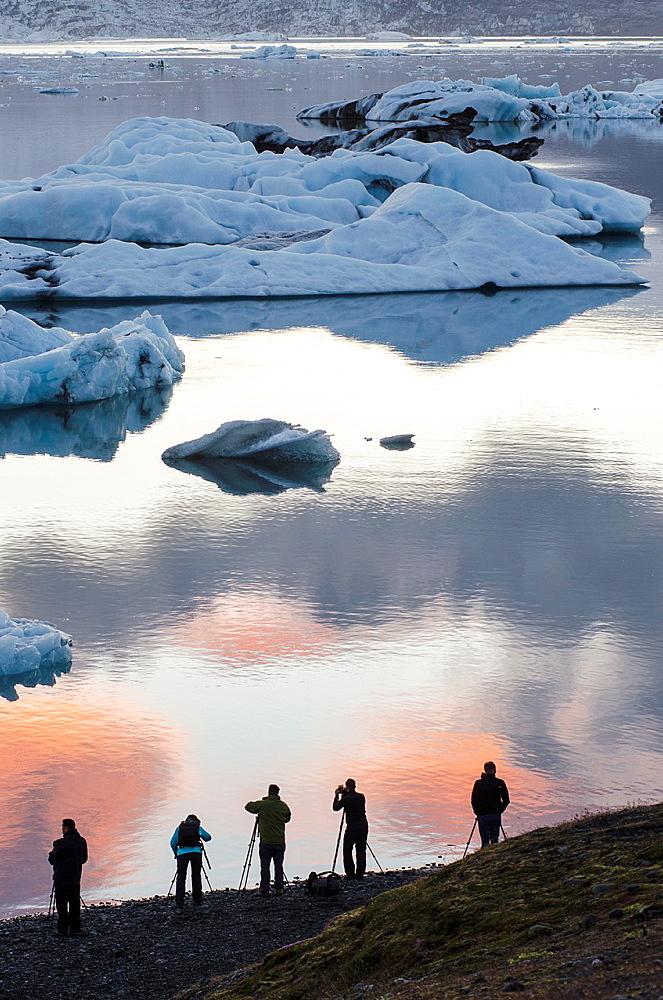 Photographers silhouette in Jokulsarlon glacial lagoon, Iceland