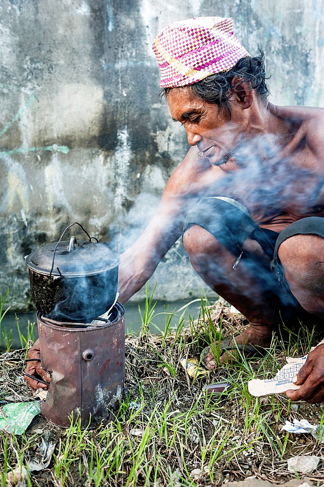 Homeless man cooking in the streets of Cebu, Visayas, Philippines, South East Asia